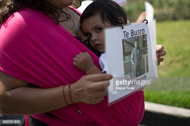 A woman holds a photograph of her disappeared husband during a march on Mother's Day on May 08 2016 in Mexico City Mexico Mothers and other relatives...