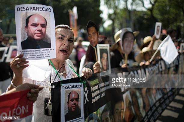 A woman holds a photograph of her disappeared son during a march on Mother's Day on May 08 2016 in Mexico City Mexico Mothers and other relatives of...