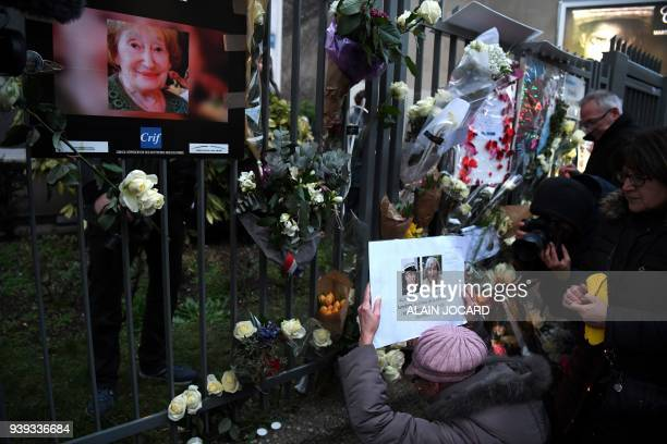 A woman holds a photograph of slain LieutenantColonel Arnaud Beltrame and Mireille Knoll as she gathers with others at the entrance to an apartment...