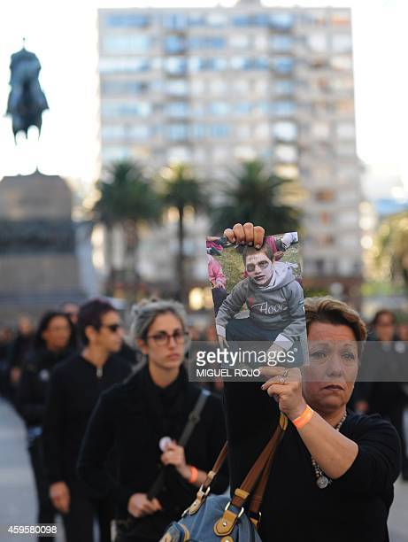 A woman holds a picture during a march called by Mujeres de Negro association to commemorate UN's International Day for the Elimination of Violence...