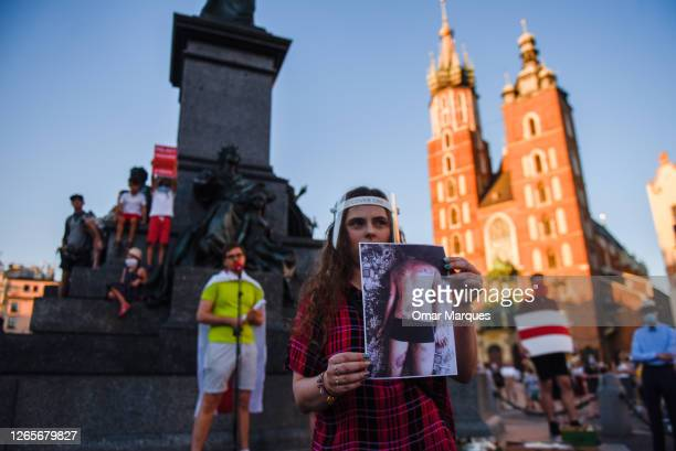 A woman holds a picture of a tortured man during a protest against the Presidential election results and police violence in Belarus at Krakow's...