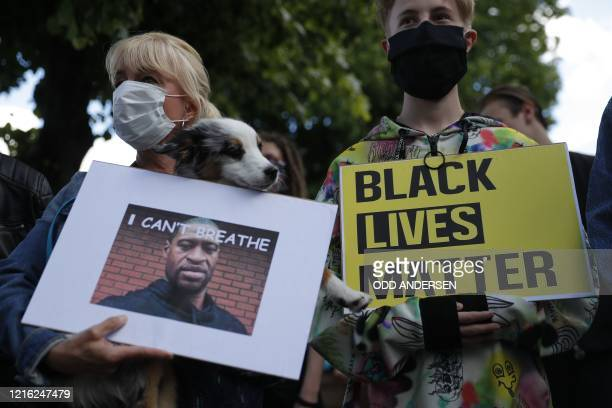 A woman holds a picture of George Floyd reading I can't breathe and a young man a sign reading Black lives matter at a protest in front of the US...