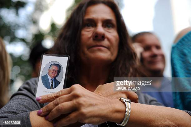 A woman holds a picture of her husband who died during September 11 terrorist attacks as she along with other victims family members waits for Pope...