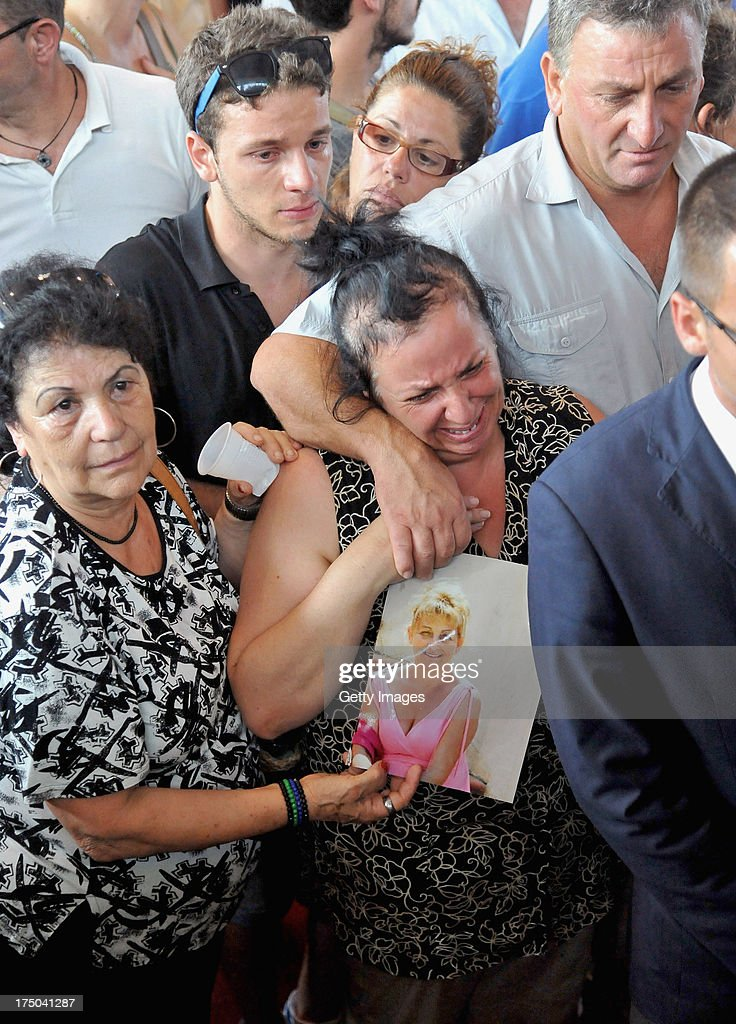 A woman holds a picture of one the victim's during the funeral of the victims of the Monteforte Irpino coach crash held at a local indoor sports arena on July 30, 2013 in Pozzuoli, Italy. In the second major European transport disaster in a week, 39 people were killed when a coach bus fell from a viaduct near Monteforte Irpino, Italy on July 28.
