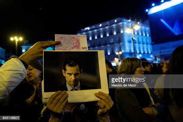 A woman holds a picture of Urdangarin during a protest against corruption case Noos