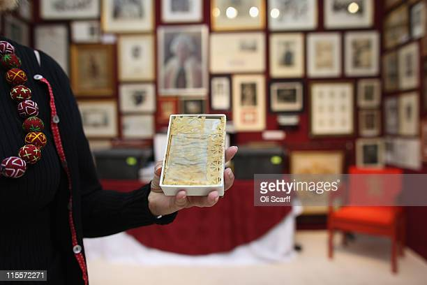 A woman holds a piece of wedding cake from the wedding of Prince Charles and Princess Diana in 1981 at the Olympia International Fine Art and...