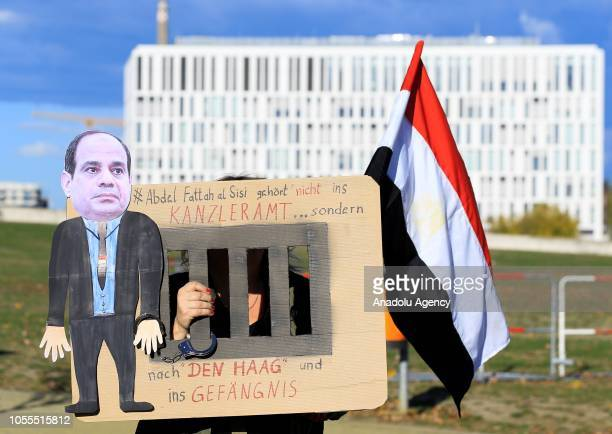 A woman holds a placard as a group of protesters stage a protest against President of Egypt Abdel Fattah elSisi outside the Chancellery during his...
