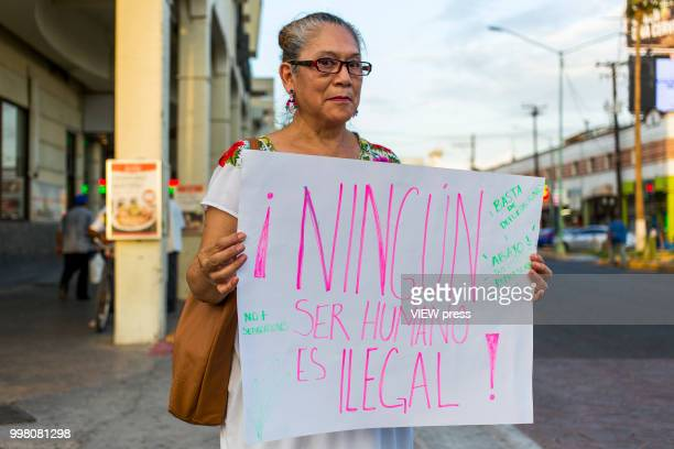 A woman holds a placard as demonstrators take part in a protest against US president Donald Trump migration policies in the border between Mexico and...