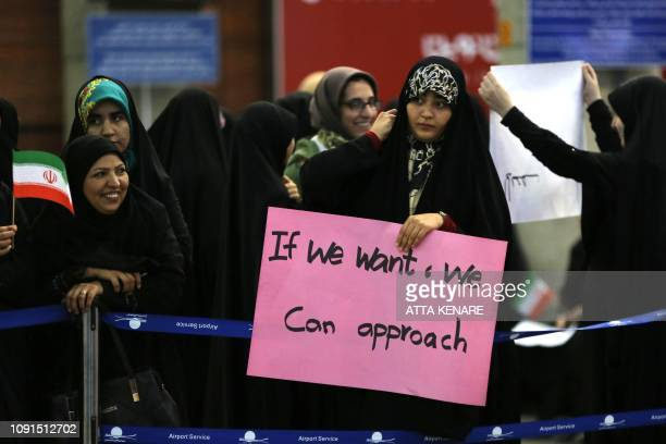 A woman holds a placard as journalist Marzieh Hashemi arrives at Tehran Imam Khomeini International Airport in Tehran on January 30 2019 The USborn...