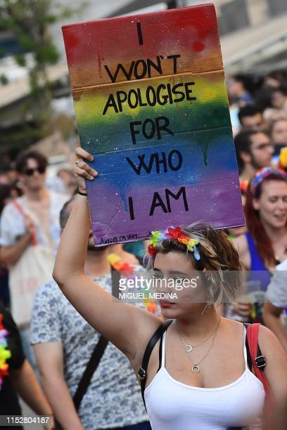 A woman holds a placard as people parade during the Milan Pride 2019 on June 29 2019 in Milan as part of the LGBT Pride month marking the 50th...