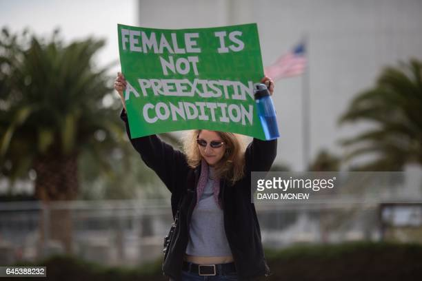 A woman holds a placard as people protest Trump administration policies that threaten the Affordable Care Act Medicare and Medicaid near the Wilshire...