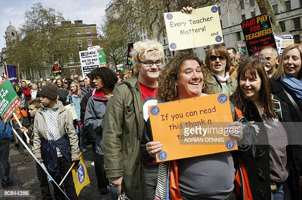 A woman holds a placard as she marches along Whitehall during the teachers and general workers protest in central London on April 24 2008 Thousands...