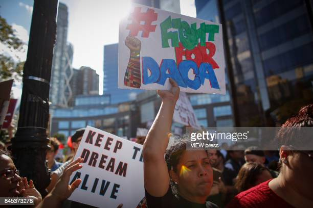 A woman holds a placard as she takes part during a march in protest of President Trump's decision on DACA in front of a Trump Hotel on September 9...