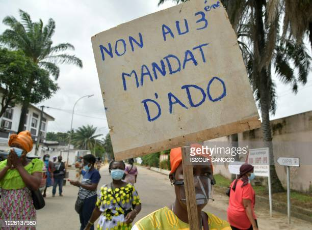 Woman holds a placard as supporters of the Democratic Party of Ivory Coast African Democratic Rally and Ivorian Popular Front try to protest against...