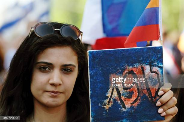 A woman holds a placard bearing the date 1915 during a march in commemoration of the 103rd anniversary of the mass killings of Armenians by Ottoman...