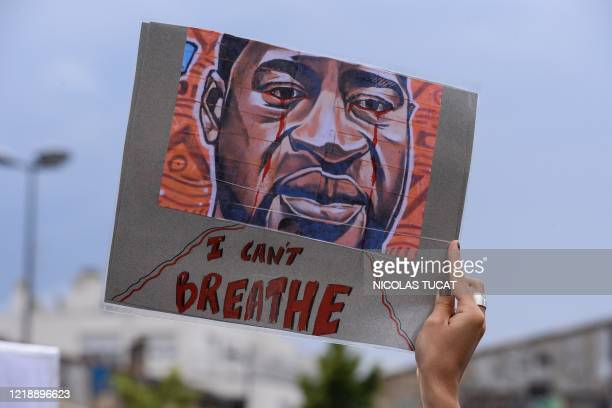 A woman holds a placard depicting George Floyd's face and reading I can't breathe in Bordeaux on June 9 during a demonstration against racism and...