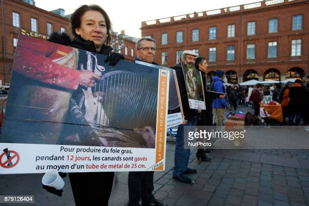 A woman holds a placard depicting gooses in a farm and reading 'to produce foie gras ducks are fed during 12 days with a metal tub' The L214...