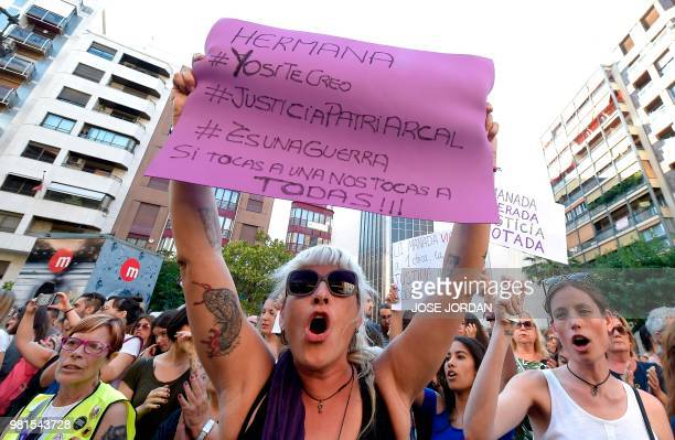 A woman holds a placard displaying hashtags for social media during a demonstration in Valencia on June 22 after a court ordered the release on bail...