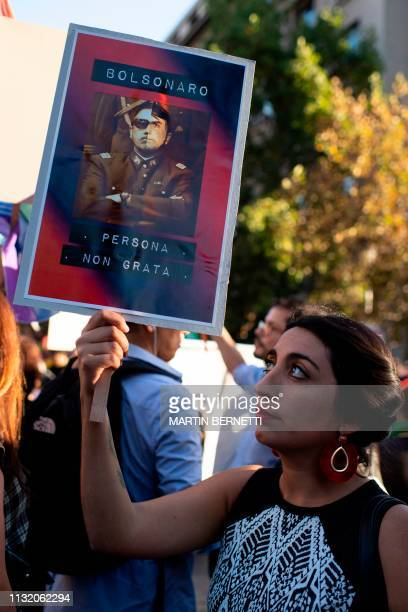 A woman holds a placard during a protest called by Women and LGTB activists againts Brazilian President Jair Bolzonaro's visit in front of La Moneda...