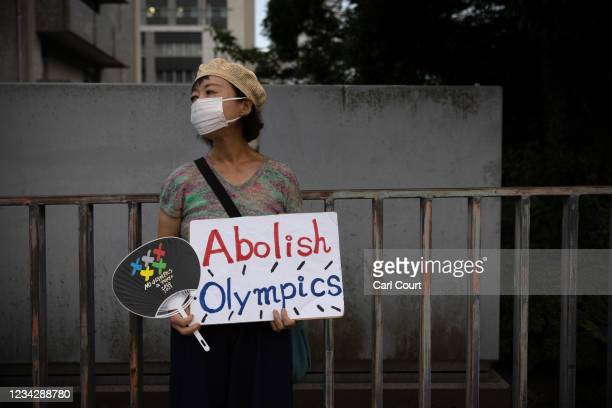 Woman holds a placard during an anti-Olympics protest outside the official residence of Japan's Prime Minister, Yoshihide Suga, on July 29, 2021 in...