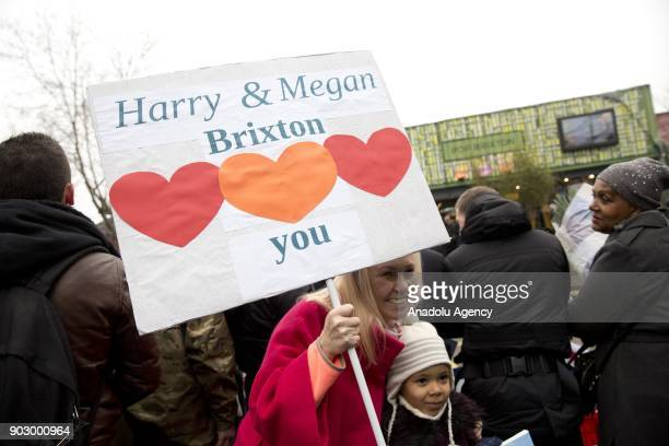 A woman holds a placard during Prince Harry and his fiance Meghan Markle's arrival to Pop Brixton to see the broadcaster's work supporting young...