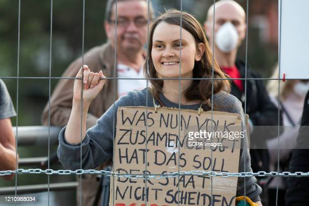 A woman holds a placard during the demonstration Hundreds of polishGermany border residents protest against antivirus measures as they block them...