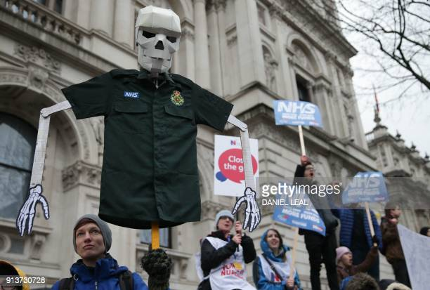 A woman holds a placard featuring a skeleton wearing a NHS uniform on Whitehall during a protest calling for an end to the 'crisis' in the staterun...