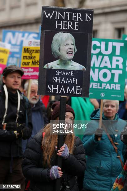 A woman holds a placard featuring the face of Britain's Prime Minister Theresa May during a protest calling for an end to the 'crisis' in the...