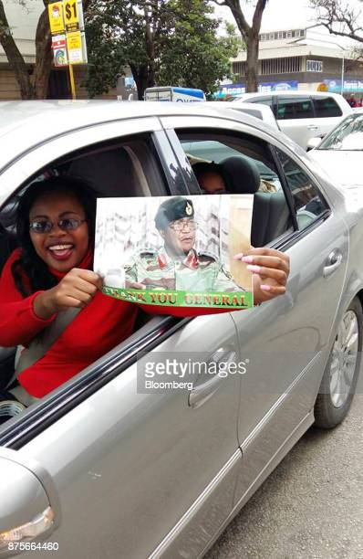 A woman holds a placard from a car window depicting ConstantineChiwenga commander of the Zimbabwe defence forces in Harare Zimbabwe on Saturday Nov...