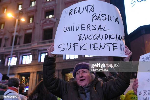 A woman holds a placard in favour of universal basic income during the protest Hundreds of people gathered at Callao square in Madrid to mark the...