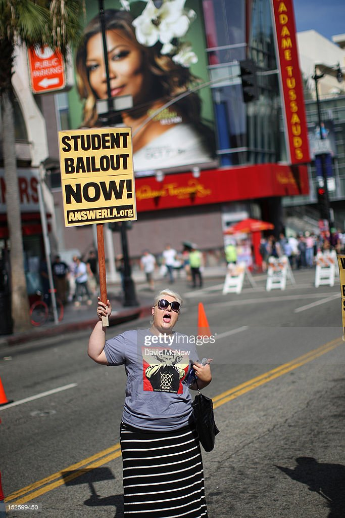 A woman holds a placard on Hollywood Boulevard while protesting the rising costs of student loans for higher education on September 22, 2012 in the Hollywood section of Los Angeles, California. Citing bank bailouts, the protesters called for student debt cancelations.