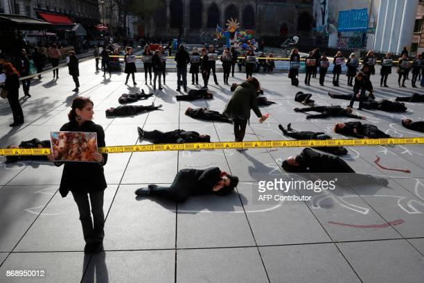 A woman holds a placard picturing dead young chicken as she stands next to people lying on the floor in order to represent an animal crime scene at...