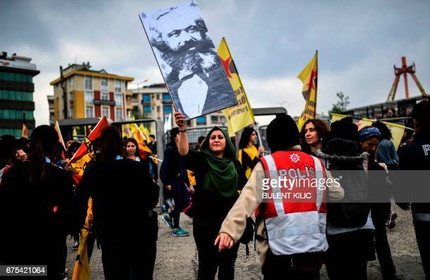 A woman holds a placard picturing German philosopher and communist theoretician Karl Marx as she takes part in a gather in Bakirkoy district as part...