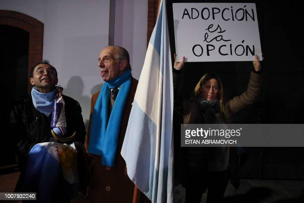 A woman holds a placard reading 'Adoption is the Option' as people demonstrate against the legalization of abortion in front of the presidential...