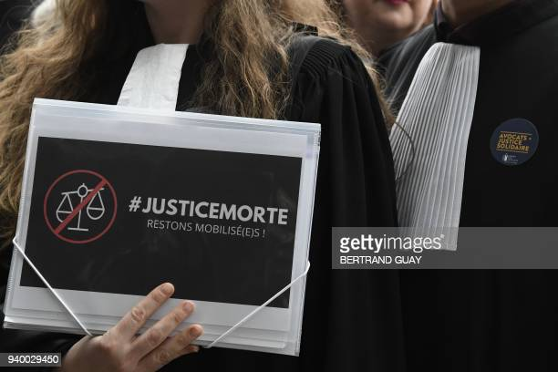 A woman holds a placard reading #DeadJustice as lawyers and magistrates gather at the entrance hall of the courthouse in Nanterre outside Paris on...
