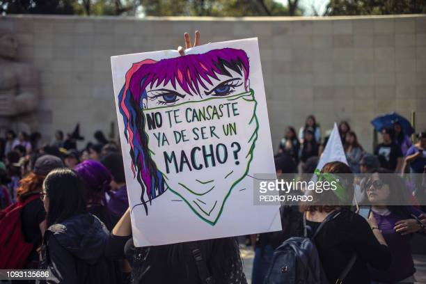 "Woman holds a placard reading ""didn't you get tired of being a macho?"" a protest against gender violence and femicides in Mexico City on February 2,..."
