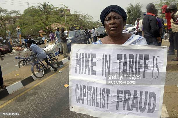 A woman holds a placard reading Hike in tariff is capitalist fraud during a demonstration to protest against the 45 percent raise of electricity...