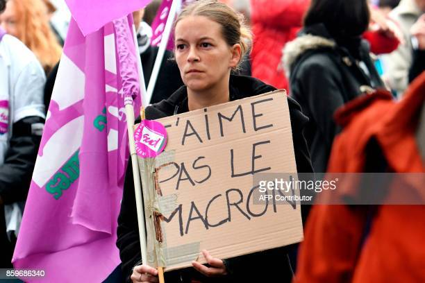"""Woman holds a placard reading """"I dislike Macron"""", as part of a nation-wide action day of French civil servants against government's plans to freeze..."""