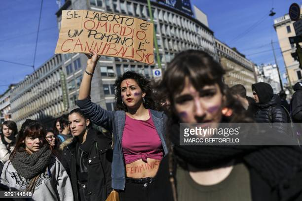 A woman holds a placard reading 'If abortion is murder blowjob is cannibalism' during the Women March against Violence as part of International...