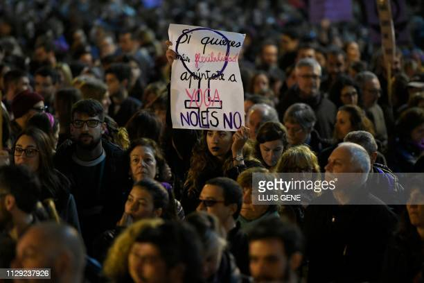 A woman holds a placard reading 'If you want more flexibility go to Yoga classes NO is No' during a demonstration marking International Women's Day...