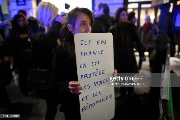 A woman holds a placard reading 'In France rapists and pedophiles are protected by law' during a demonstration to call for a legislative change to...