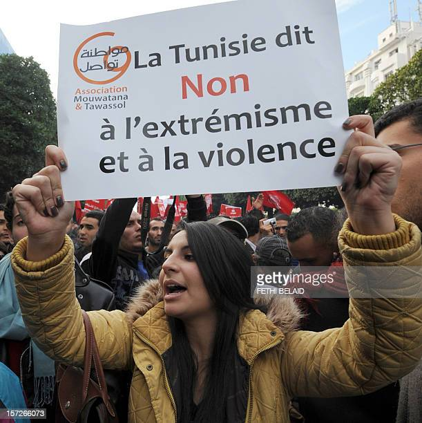 A woman holds a placard reading in French 'Tunisia says No to extremism and violence' during a demonstration in front of the Interior Ministry in...