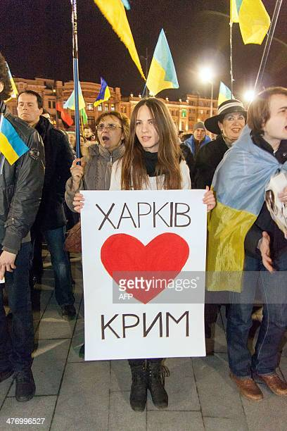 A woman holds a placard reading 'Kharkiv loves Crimea' while ProUkrainian activists sing the state anthem during a rally in the center of the eastern...