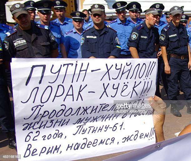 """Woman holds a placard reading """"Life expectancy for men in Russia is 62 years. Putin is 61. Believe, hope, wait!!!"""" and the other untranslatable..."""
