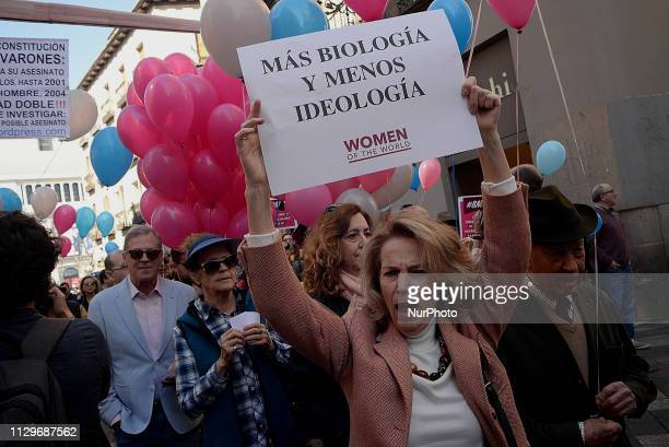 A woman holds a placard reading 'More biology and less ideology' during the demonstration against feminism in Madrid on 10th March 2019 The...