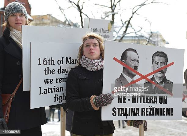 A woman holds a placard reading ' No to Hitler and Stalin regimes' on March 16 2014 to protest against the annual march of veterans of the Latvian...