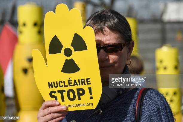 A woman holds a placard reading 'Nuclear Stop' during a demonstration to demand the closure of Fessenheim nuclear power plant on March 12 2017 / AFP...