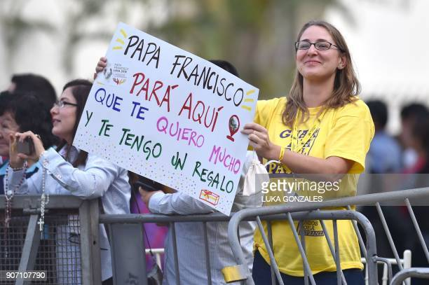 A woman holds a placard reading 'Pope Francis Stop Here That I Love Your So Much and I've Got a Present For You' as the pontiff greets the crowd from...