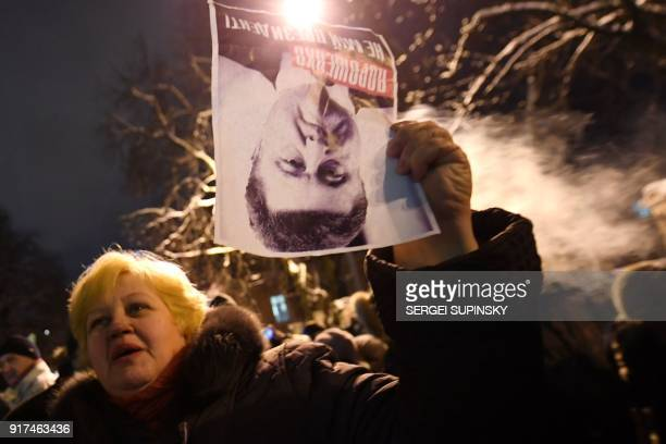 A woman holds a placard reading 'Poroshenko is not our president' as supporters of former Georgian President Mikheil Saakashvili demonstrate in front...