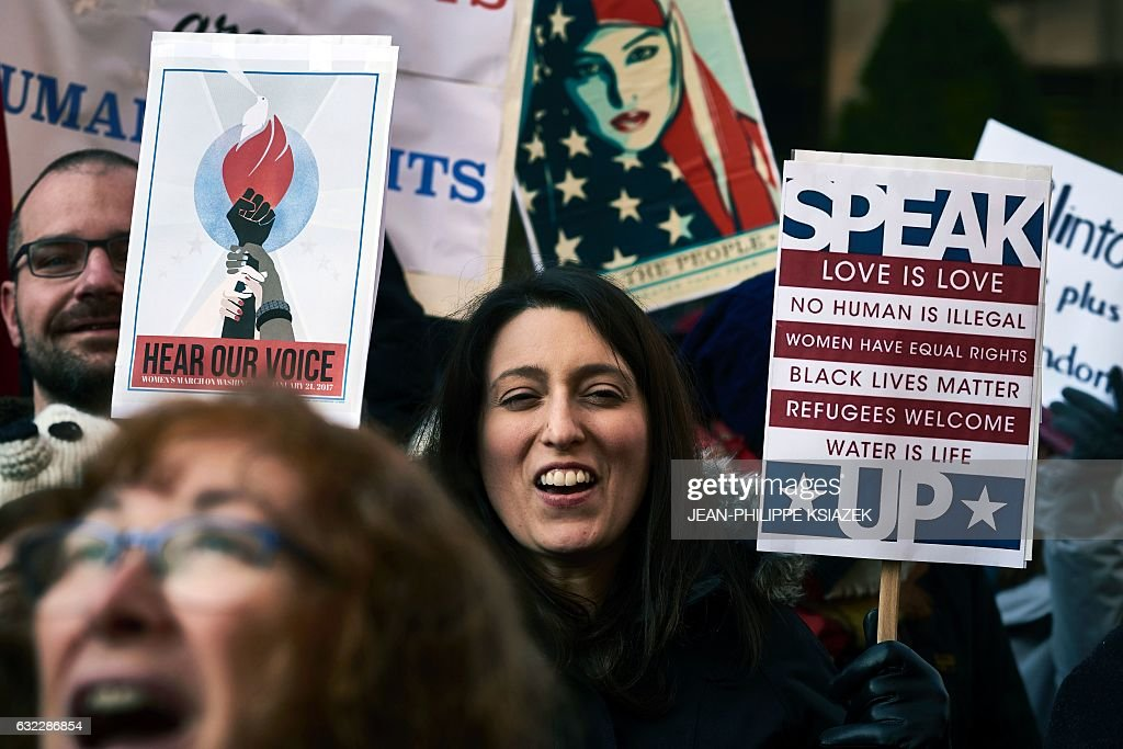 A woman holds a placard reading 'SPEAK love is love, no human is illegal, women have equal rights, black lives matter, refugees welcome, water is life, UP' during a rally in solidarity with the Women's March taking place in Washington and many other cities on January 21, 2017 in Lyon, southeastern France, one day after the inauguration of the US President. Protest rallies were held in over 30 countries around the world in solidarity with the Washington Women's March in defense of press freedom, women's and human rights following the official inauguration of Donald J Trump as the 45th President of the United States of America. / AFP / JEAN